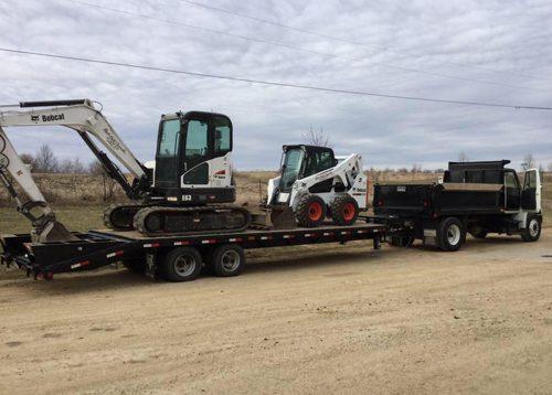rock Solid Concrete equipment including bobcat, truck, and excavator