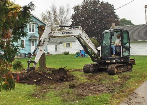 Tree removal with white Rock Solid Concrete bobcat